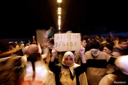 "A woman takes part in a protest demanding immediate political change, in Algiers, Algeria March 12, 2019. Her sign reads: ""System, go away."""