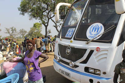 A women from South Sudan stands in front of a UNHCR passenger bus next to a refugee registration site near Bibi Bidi, Uganda, Dec. 11, 2016