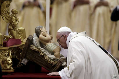 Pope Francis kisses a statue of Baby Jesus as he celebrates the Christmas Eve Mass in St. Peter's Basilica at the Vatican, Dec. 24, 2015.