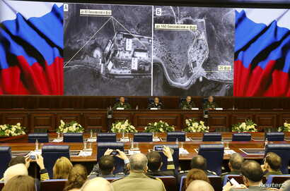 Defense ministry officials sit under screens with satellite images on display during a briefing in Moscow, Russia, Dec. 2, 2015.