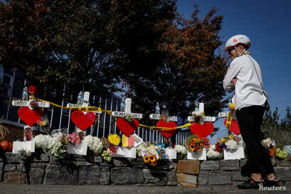 FILE - Marybeth Kelly looks at memorials along a bike path to remember the victims of the New York Oct. 31 attack, in New York City, Nov. 3, 2017.