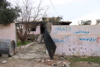 """The word """"Daeshy,"""" meaning IS militant, is scrawled on a burnt-out house once belonging to a militant in a village outside of Mosul city in Iraq, Nov. 27, 2018."""
