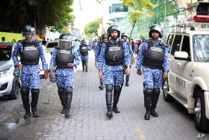 FILE - Maldivian policemen patrol the area where supporters of former president Mohamed Nasheed have gathered for a mass rally in Male', Maldives on Nov.  27, 2015.