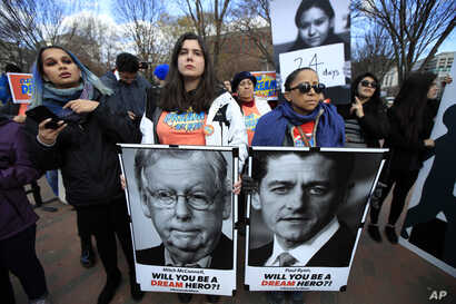 FILE - Amanda Bayer, left holding banner, and Marisol Maqueda, right with banner, from Mexico whose daughter Maria Torres also from Mexico City is a DACA recipient finishing her masters degree in Arizona, join a rally outside the White House in Washi...