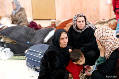 Civilians who escaped from Islamic State militants rest at a mosque in Raqqa, Syria, Oct. 12, 2017.