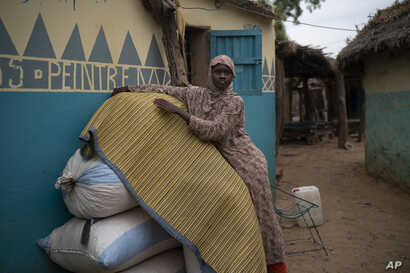 FILE - Mariama Konte, 20, stands inside her home in a village near Goudiry, Senegal, Nov. 26, 2018. Konte, who married Abdrahamane when she was 12 and he was 21, is living the consequences of the family's decision in November to mourn him after nearl...