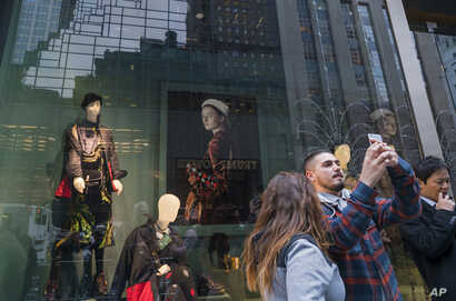 People take photos across Fifth Avenue of Trump Tower (reflected in window) in New York, Nov. 9, 2016. Donald Trump claimed his place Wednesday as America's 45th president, an astonishing victory for the celebrity businessman and political novice who...