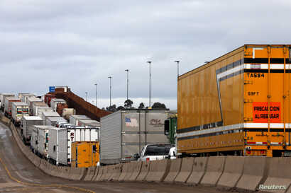Trucks wait in a long queue at border customs control to cross into the U.S. at the Otay border crossing in Tijuana, Mexico, April 3, 2019.