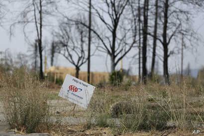 In this photo taken , Aug. 9, 2018, a sign from an insurance company sits at the edge of a Santa Rosa, Calif., property that was destroyed in the deadly October 2017 wildfires.