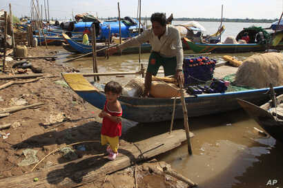 FILE - A man and grandchild prepares fishing nets at the Kbal Chroy village on the Mekong River bank near Phnom Penh, Cambodia, May 17, 2018.
