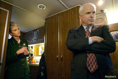 Republican presidential candidate Arizona Senator John McCain (R) listens to advice from his campaign staff onboard his bus as his wife Cindy (L) looks on near Concord, New Hampshire January 25.