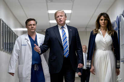 President Donald Trump, center, accompanied by first lady Melania Trump, right, and Dr. Igor Nichiporenko, left, speak to reporters while visiting with medical staff and victims of a mass shooting at a local school in Pompano Beach, Fla., Feb. 16, 20...