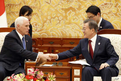 U.S. Vice President Mike Pence, left, shakes hands with South Korean President Moon Jae-in during their meeting at the presidential office Blue House in Seoul, Feb. 8, 2018.