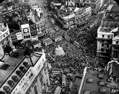 A crowd gathers to celebrate V-E Day at Piccadilly Circus in London, England, on May 8, 1945.