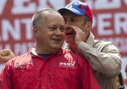 Government politician Diosdado Cabello listens to Venezuela's Vice President Tareck El Aissami at a rally opposing the United States and possible OAS sanctions, in Caracas, Venezuela, March 28, 2017.