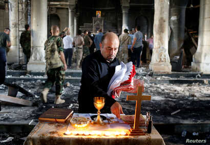 An Iraqi Christian prepares for the first Sunday mass at the Grand Immaculate Church since it was recaptured from Islamic State in Qaraqosh, near Mosul in Iraq, Oct. 30, 2016.