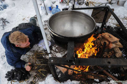 A man makes a fire under a large cooking pot in the Oceti Sakowin camp during the protest of the Dakota Access pipeline, Nov. 29, 2016.