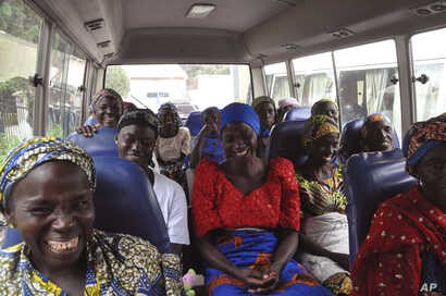 FILE - Family members of the Nigerian Chibok kidnapped girls share a moment as they depart to the Nigerian minister of women affairs in Abuja, Nigeria, Oct. 18, 2016. Nigeria's government is negotiating the release of another 83 of the Chibok school...