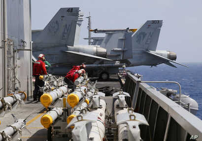 FILE - U.S. Navy crewmen from the U.S. Navy aircraft carrier USS Carl Vinson (CVN 70) prepare to load missiles to F-18 fighter jets prior to a routine patrol off the disputed South China Sea Friday, March 3, 2017. Philippines South China Sea-US Milit...
