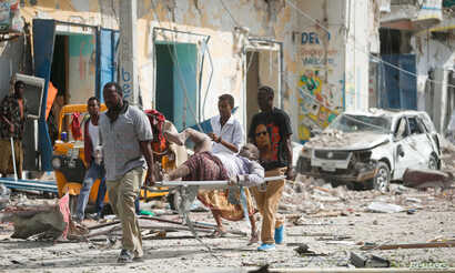 Rescuers carry an unidentified injured man from the scene of an explosion in front of Dayah hotel in Somalia's capital Mogadishu, Jan. 25, 2017.