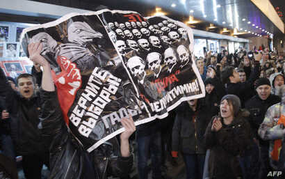 "Opposition demonstrators hold a poster reading ""Give back the elections, rascals"" during protests against alleged vote rigging in Russia's parliamentary elections in Triumphal Square  in Moscow, Russia, Tuesday, Dec. 6, 2011. Police clashed Tuesday o..."