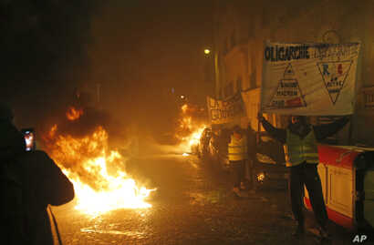 Demonstrators wearing yellow vests hold banners next to burning barricades near the Champs-Elysees during a yellow vest protest in Paris, Jan. 5, 2019.