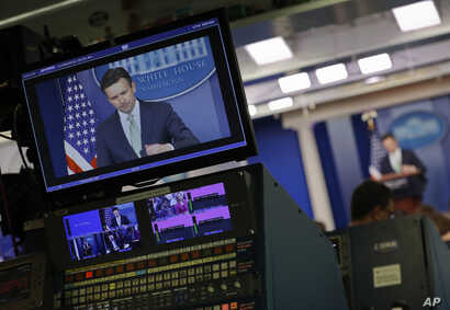 White House press secretary Josh Earnest is seen on broadcast television monitors as he begins to speak to the media during the daily briefing in the Brady Press Briefing Room of the White House, Nov. 9, 2016.