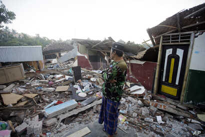 A man inspects the ruins of his house destroyed by an earthquake in North Lombok, Indonesia, Aug. 9, 2018.