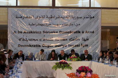 """Participants attend a conference held by the Democratic Forces of Syria in Derek, Syria, Dec. 8, 2015. The text on the banner reads in Arabic, """"Democratic Syria conference for Opposition forces, towards building a free democratic Syria."""""""