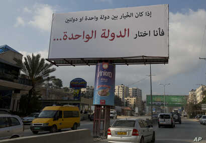 "FILE - Motorists pass a banner supporting the creation of a single state for Israelis and Palestinians that reads in Arabic: ""If I had to choose between one state and two states, I would choose the one state,"" in the West Bank city of Ramallah, Feb. ..."