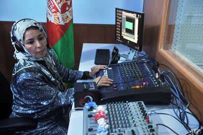 "FILE - Female Afghan journalist works in the studio of ""Shahrzad,"" the second radio station to be dedicated to the interests of women, Herat, Oct. 14, 2012."