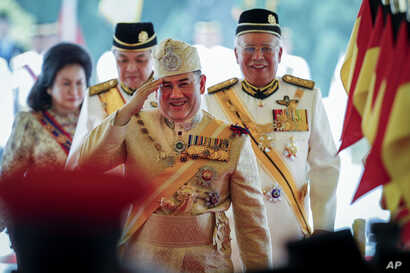 Sultan Muhammad V, center, salutes after his welcome ceremony as he walks with Malaysian Prime Minister Najib Razak, right, at the Parliament House in Kuala Lumpur, Malaysia, Dec. 13, 2016.
