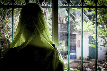 Diakite, 46, looks out the window after her annual check up with Dr. Abdoul Aziz Kasse at the Clinique des Mamelles in Dakar, Senegal on July 13, 2017. Diakite has successfully recovered from cervical cancer thanks to Dr. Kasse and yearly checks.