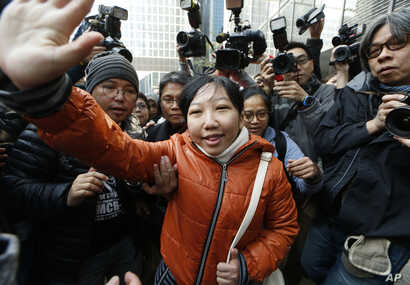 Indonesian maid Erwiana Sulistyaningsih, center, waves to her supporters as she arrives at a court in Hong Kong, Feb. 10, 2015.
