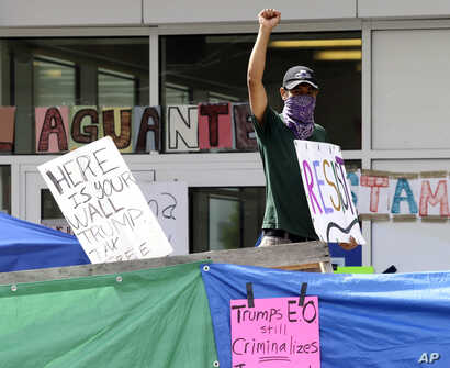 An unidentified man holds a sign behind a makeshift wall at a protest camp on property outside the U.S. Immigration and Customs Enforcement office in Portland, Ore., June 25, 2018. The round-the-clock demonstration outside the office began June 17.