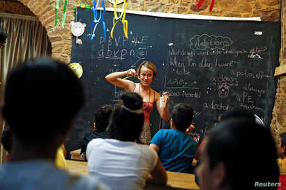 """British volunteer primary school teacher Helen Brannigan holds a pen and a cup as she conducts an English class for refugee children at the volunteer-run """"Refugee Education Chios"""" school on the island of Chios, Greece, Sept. 6, 2016."""