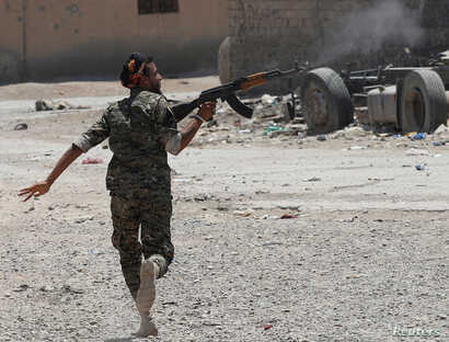 A Kurdish fighter from the People's Protection Units (YPG) fires his rifle at Islamic State militants as he runs across a street in Raqqa, Syria, July 3, 2017.