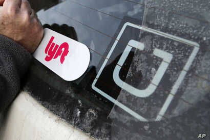 "FILE - A Lyft logo is installed on a Lyft driver's car next to an Uber sticker in Pittsburgh, Jan. 31, 2018. The ""gig"" economy might not be the new frontier for America's workforce after all."