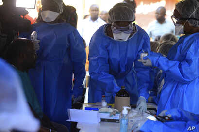 Healthcare workers from the World Health Organization prepare to give an Ebola vaccination to a front line aid worker in Beni Democratic Republic of Congo, Aug 10, 2018.