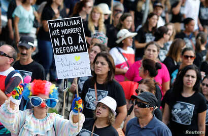 "Demonstrators protest during a strike against Brazilian Social Welfare reform project, in Curitiba, Brazil March 15, 2017. The placard reads: ""Work until die? No to reform."""