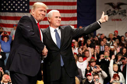 U.S. President-elect Donald Trump shakes hands with Vice President-elect Mike Pence (R) at the USA Thank You Tour event at the Iowa Events Center in Des Moines, Iowa, Dec. 8, 2016.