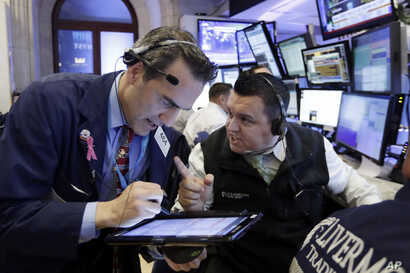 Traders Gregory Rowe, left, and Robert Finnerty work on the floor of the New York Stock Exchange, Nov. 9, 2016. Stocks are moving solidly higher in midday trading on Wall Street following Donald Trump's upset victory over Hillary Clinton in the U.S. ...