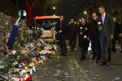 President Barack Obama, right, French President Francois Hollande, second from right, and Paris Mayor Anne Hidalgo arrive at the Bataclan, site of one of the Paris terrorists attacks, to pay their respects to the victims, Nov. 30, 2015.