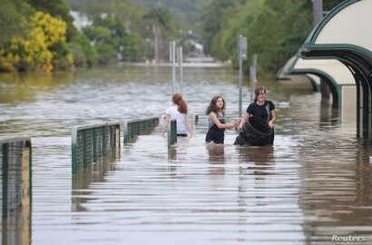Locals walk through a flooded street in the northern New South Wales town of Lismore, Australia, April 1, 2017, after heavy rains associated with Cyclone Debbie swelled rivers to record heights across the region.