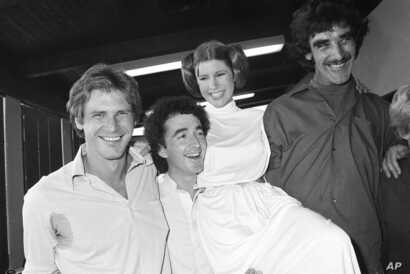 """FILE - Actor Harrison Ford, left, who played Han Solo in the move """"Star Wars,"""" is pictured with his co-stars, Anthony Daniels, who played C-3P0; Carrie Fisher, who played Princess Leia; and Peter Mayhew, who played Chewbacca, as they take a break fro..."""