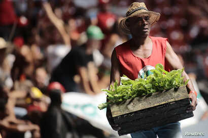 FILE - A member of the Landless Workers Movement attends the opening ceremony of its 6th National Congress in Brasilia, Brazil, Feb. 10, 2014.