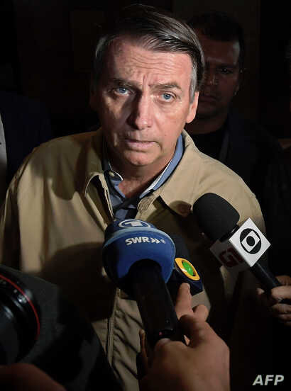 Brazilian far-right presidential candidate Jair Bolsonaro speaks to the press during a visit to the Federal Police station in Rio de Janeiro, Oct. 17, 2018.