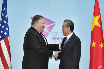 U.S. Secretary of State Mike Pompeo, left, and China's Foreign Minister Wang Yi shake hands ahead of a bilateral meeting on the sidelines of the 51st ASEAN Foreign Ministers Meeting in Singapore, Aug. 3, 2018.