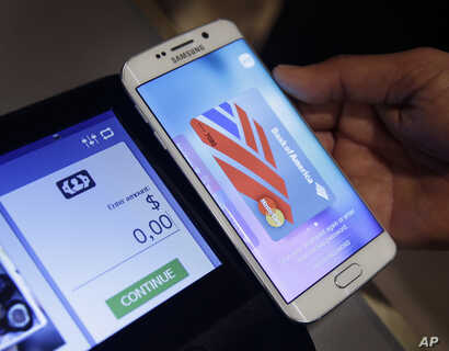 FILE - A Samsung employee demonstrates Samsung Pay using a Galaxy S6 Edge Plus in New York, Aug. 6. 2015.