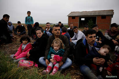 FILE - Syrian refugees who crossed the Evros river, the natural border between Greece and Turkey, rest on a field as they wait for the police to arrive and transfer them to a first reception center, near the village of Nea Vyssa, Greece, May 2, 2018....